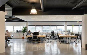 werknemers kantoorruimte op maat kantoorgebouw hogehilweg amsterdam zuidoost bureau's stoelen medewerkers witte palen vloer