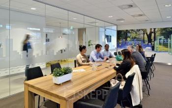 vergadering personen lang tafel stoelen gemeubileerde vergaderzaal kantoorgebouw karspeldreef amsterdam zuidoost
