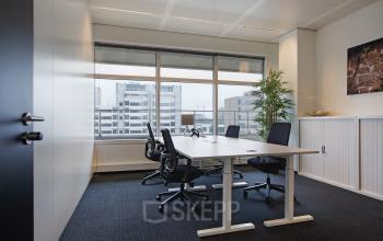 ingerichte afgesloten kantoorruimte kasten bureau soelen raam uitzicht schilderij vloerbedekking