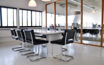 vergaderruimte tafel stoelen lampen glazen wand presentatie