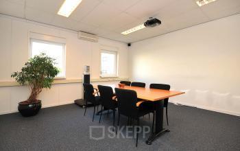 ingerichte vergaderruimte tafel stoelen raam uitzicht plant lampen vloerbedekking