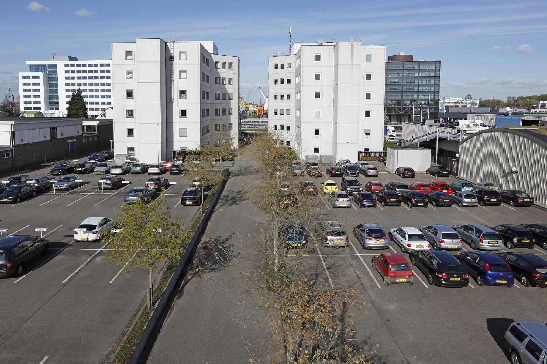 two white office buildings cars parking spots