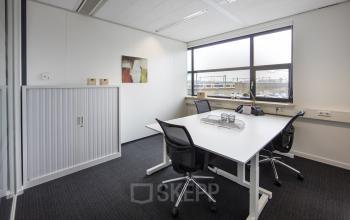 werkplek tilburg huur kantoorruimte tafel stoelen raam kast uitzicht vloerbedekking schilderij