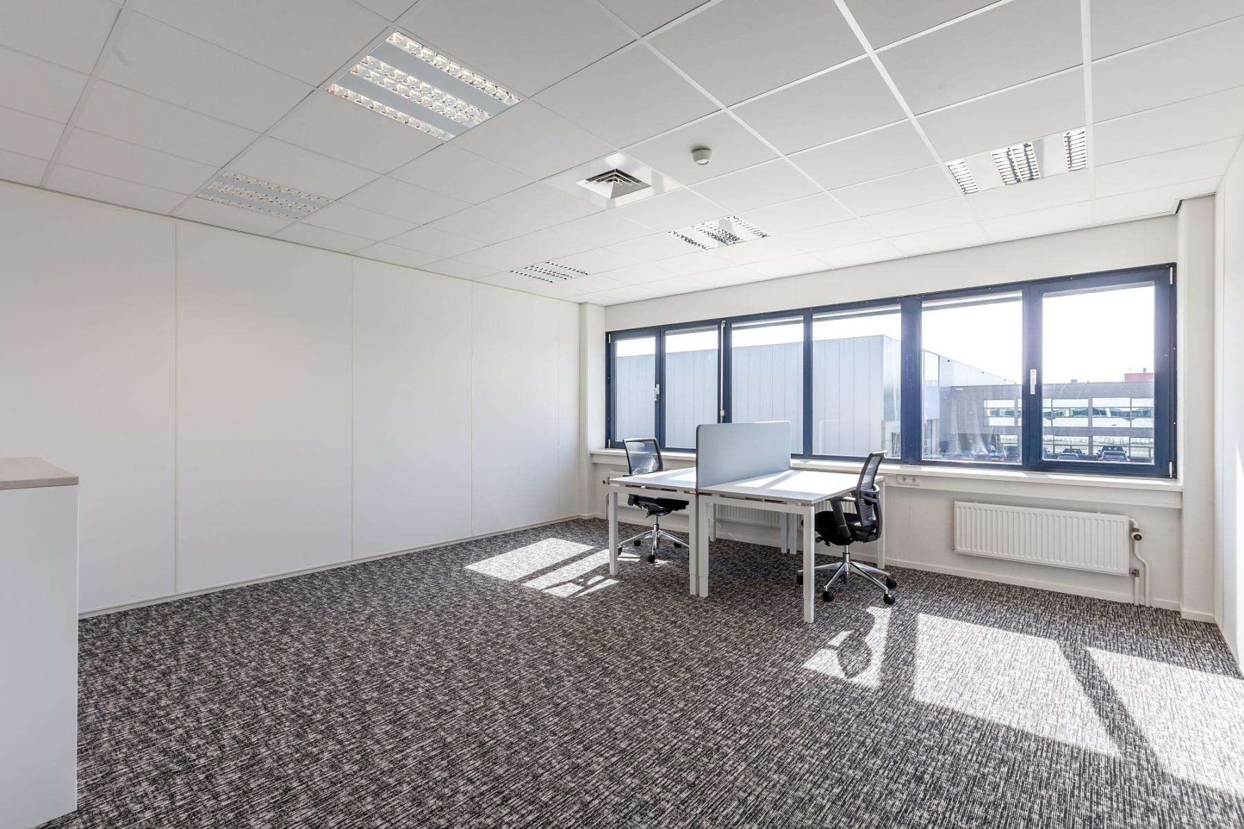 office space with large windows two people