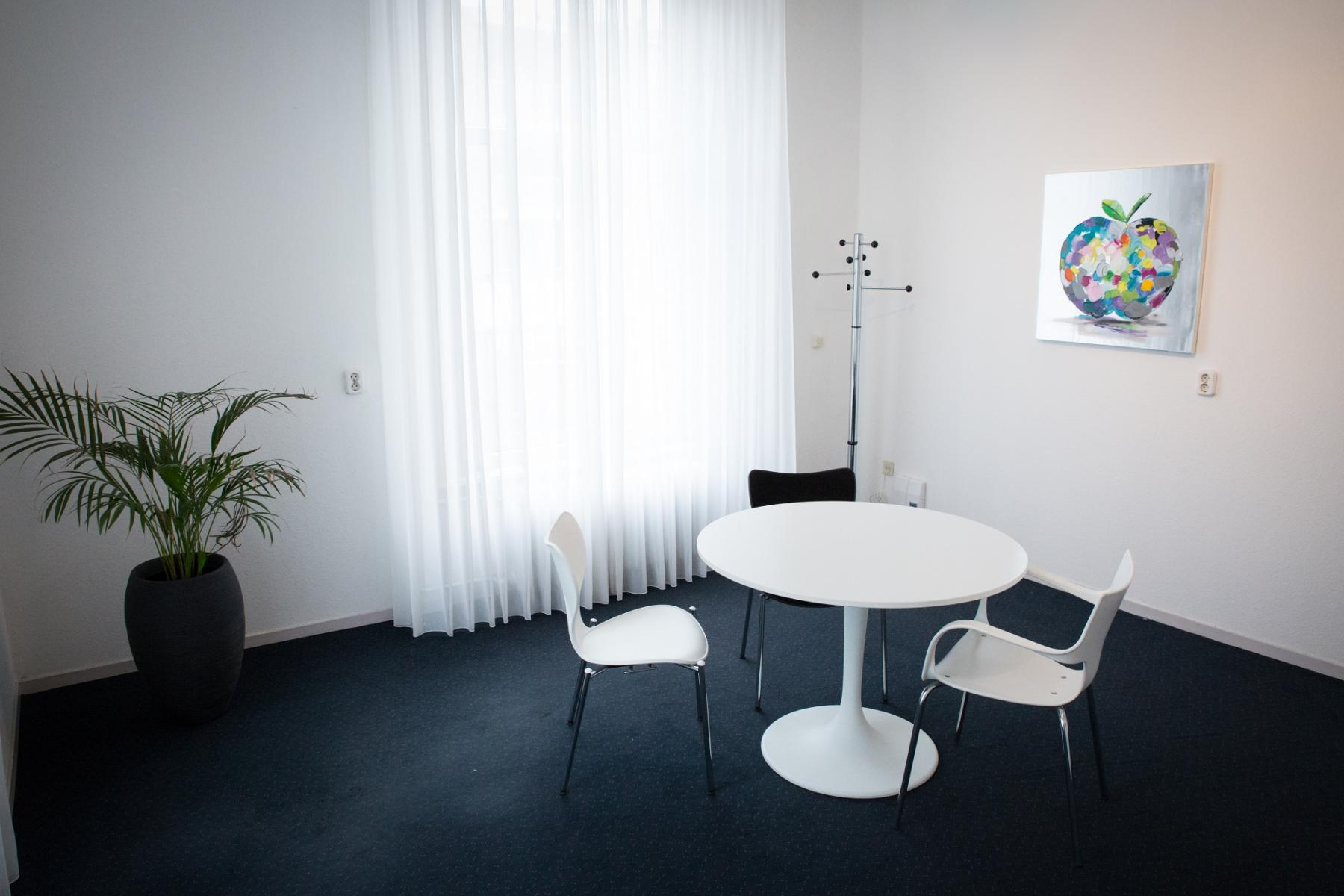 small office room with four chairs and a nice painting